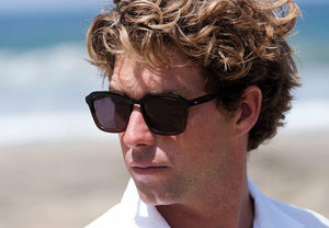 A man wearing a pair of rectangular framed glasses with a half black half brown frame and black polarized lenses and a white button up shirt in front of the beach.