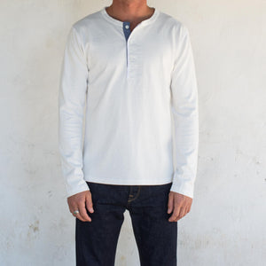 The Freenote Cloth 13 Ounce Henley Long Sleeve Shirt in White styled on an individual with dark wash denim jeans, the top button of the shirt is undone.