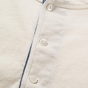 The Freenote Cloth 13 Ounce Henley Long Sleeve Shirt in White. The photo shows the three buttons near the collar closed.