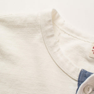 The Freenote Cloth 13 Ounce Henley Long Sleeve Shirt in White. The photo shows the side of the rounded collar.