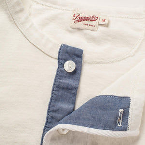 The Freenote Cloth 13 Ounce Henley Long Sleeve Shirt in White. The photo shows the top button of the shirt undone to expose a denim blue strip of fabric behind the white buttons on the shirt.