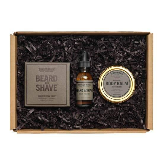 The cardboard Hudson Made Barber Box filled with black stuffing, the beard and shave soap in grey packaging, the beard and shave oil in a brown bottle with black dropper, and bronze circular container for body balm