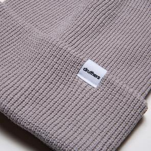 The Druthers Beanie, Cardigan Knit in Light Grey with the bottom of the beanie folded up to show the small white square logo.