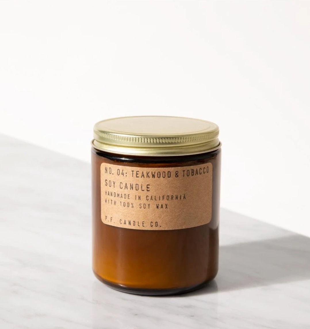 "A brown jar with a golden metal lid, a parchment colored label with typewriter font reads ""No. 4 Teakwood and Tobacco Soy Candle"""
