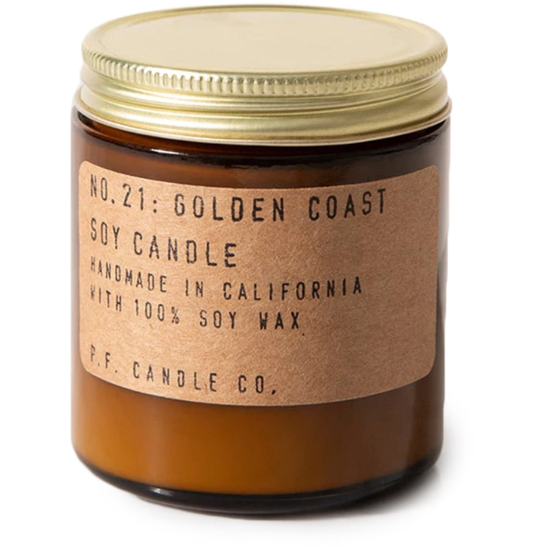 "A brown jar with a golden metal lid, a parchment colored label with typewriter font reads ""No. 21 Golden Coast Soy Candle"""