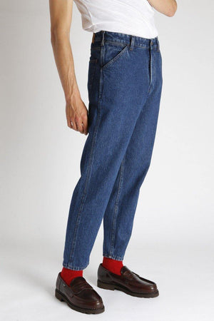 An individual wears the Homecore Jabali Algo Jeans Pants Washed with red socks and brown loafers.