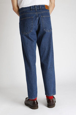 An individual wears the Homecore Jabali Algo Jeans Pants Washed with red socks and brown loafers, the back view of the pants shows two back pockets and leather logo on the waistband.