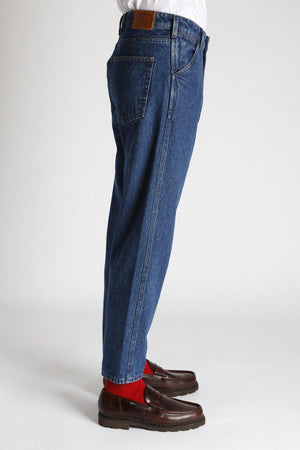 An individual wears the Homecore Jabali Algo Jeans Pants Washed with red socks and brown loafers, the side view of the individual and the pants.