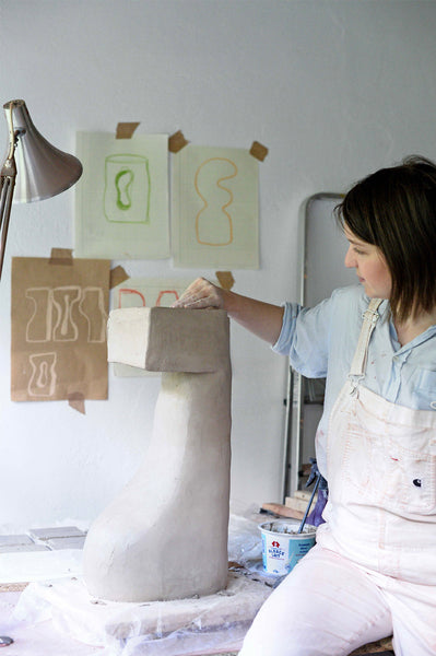 Lea Munsch with a one-of-a-kind clay sculpture in white ceramic