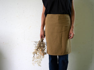 woman wearing a simple linen apron and holding dry flowers
