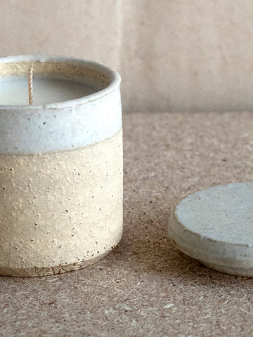 close-up of beige stoneware and white glaze scented candle at M AAH
