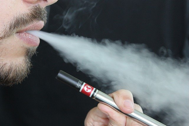 close up of person using a vape pen