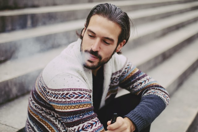 man looking to the side exhaling vape cloud