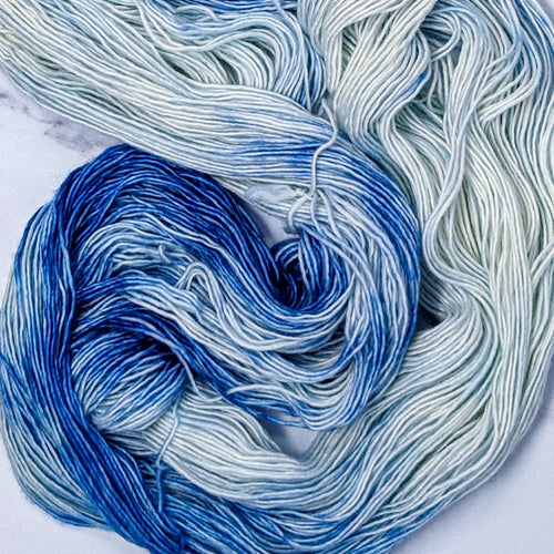 hand-dyed yarn in a variegated colorway of rich royal blue melting into pure white
