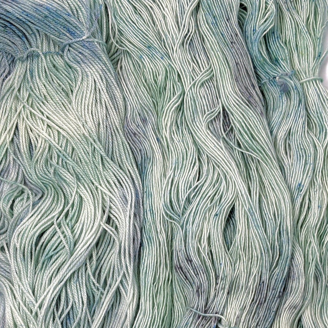 hand-dyed yarn in a variegated tonal colorway of icy blue, sea green and gray melting together like sunlight through water