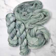 Load image into Gallery viewer, hand-dyed yarn in a variegated tonal colorway of icy blue, sea green and gray melting together like sunlight through water