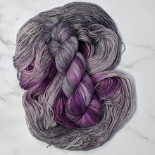 Load image into Gallery viewer, hand-dyed yarn in a variegated colorway of bursts of purple among waves of smokey gray