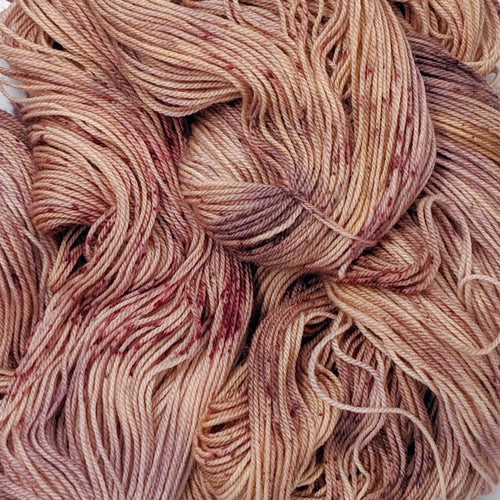hand-dyed yarn in a variegated tonal colorway of rosey tonal browns with flashes of dark rose and chestnut brown