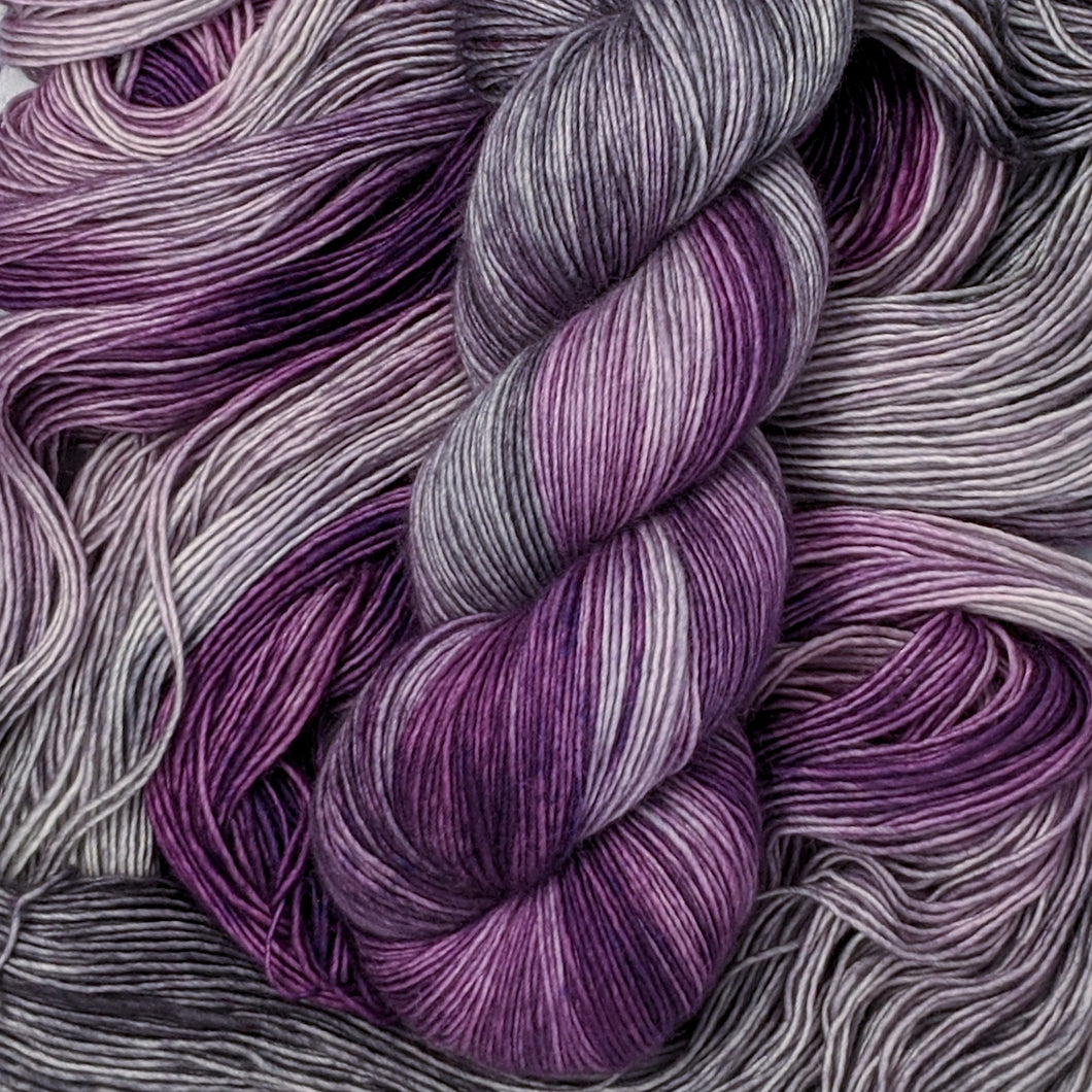 hand-dyed yarn in a variegated colorway of bursts of purple among waves of smokey gray