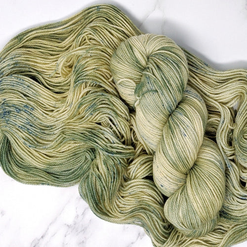 hand-dyed yarn in a variegated colorway that shifts between that unique shade of Yoda-green and pale green-cream highlights and generously dusted with a blue-sage speckles
