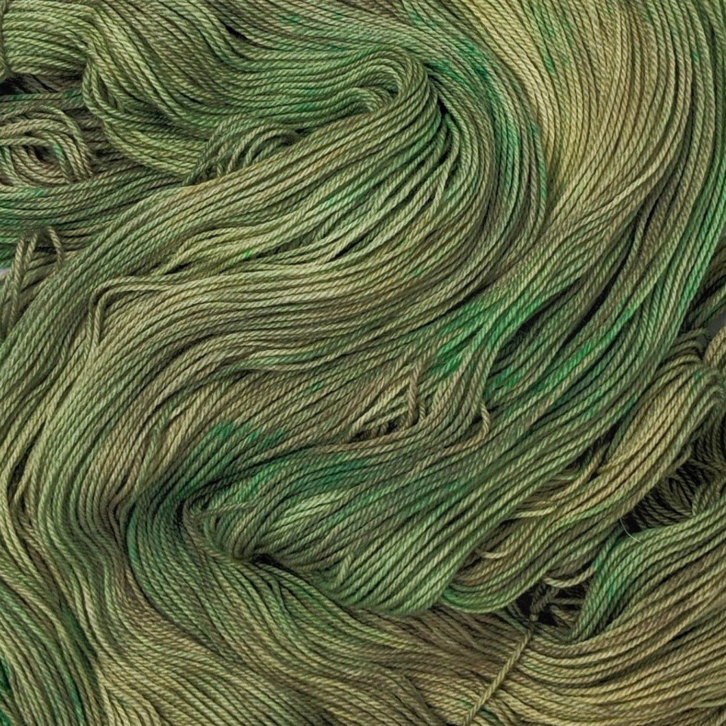 hand-dyed yarn in a variegated colorway of fully saturated shifting greens and browns