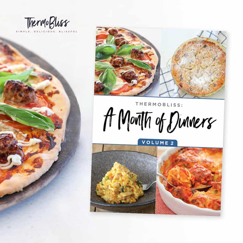 A ThermoBliss Dinners cookbook next to a pizza on a tray
