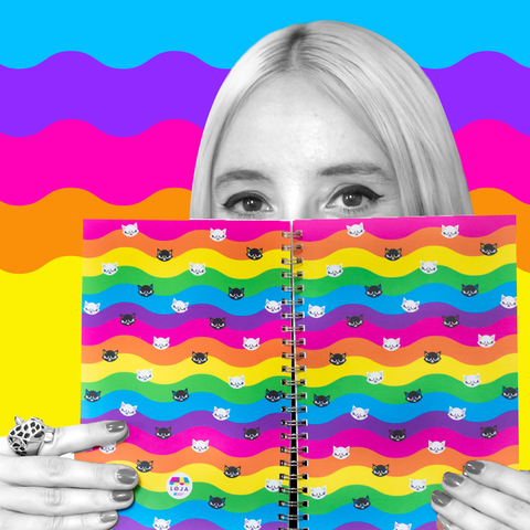 Barbara Astrini (in black & white) holding a rainbow-cat pattern notebook. Background are wavy stripes in blue, purple, pink, orange, and yellow