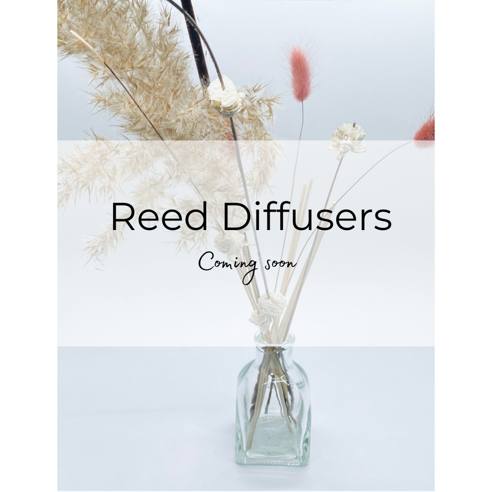 The words:  Reed Diffusers Coming soon,  super imposed on background image of a bud vase with dried botanicals and reeds on a table