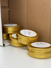 Load image into Gallery viewer, fallen stack of 5 thin gold tins pouring out of a cardboardbox; Visible labels say: Soar, Glow
