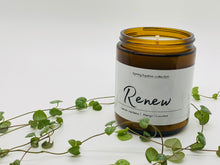 Load image into Gallery viewer, Candle in amber glass jar. Label says Renew. Fragrance notes: lemon verbena, mango, coconut