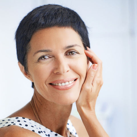 Photo of middle aged woman with beautiful skin and face looking at the camera