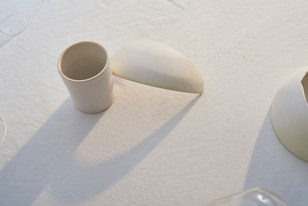 A white, handmade ceramic bowl leans against a white ceramic cup on a white linen tablecloth.