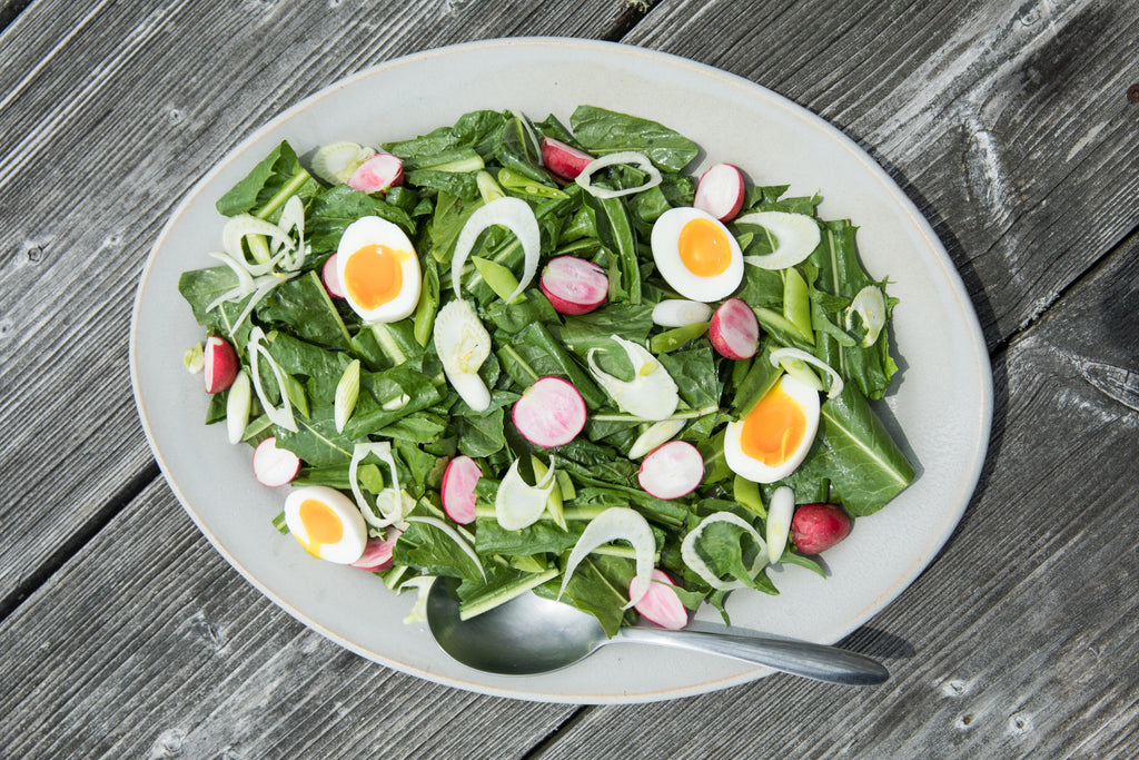 Salt Water Farm's dandelion salad plated on a handmade ceramic Farmhouse Oval Platter by Sheldon Ceramics.