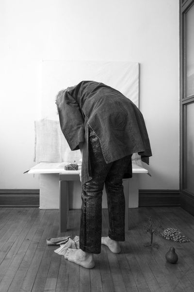 Andrea Aranow leans over a low table in her studio