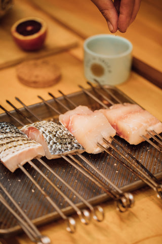 Daniel Benhaim seasons skewered filets of Japanese sea bass.