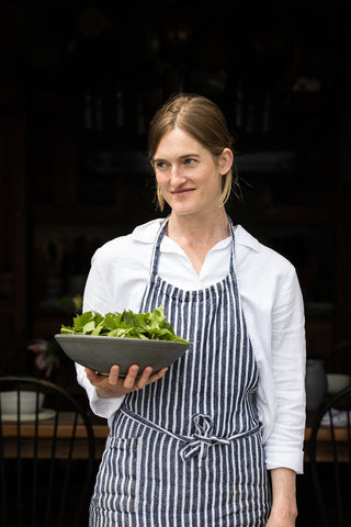 Annemarie Ahearn poses holding a handmade ceramic bowl filled with fresh parsley leaves