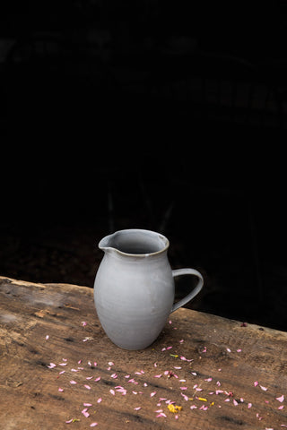 A handmade Sheldon Ceramics Farmhouse Pitcher on a rustic wooden table at Salt Water Farm