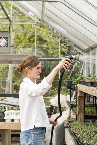 Annemarie Ahearn waters seedlings in the greenhouse at Salt Water Farm
