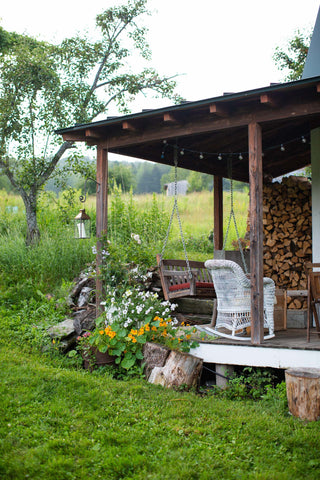 A corner of a porch at Stitchdown Farm with a porch swing and a large stack of firewood.