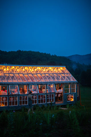 The glasshouse at night, illuminated from within against a blue-green, hilly backdrop.