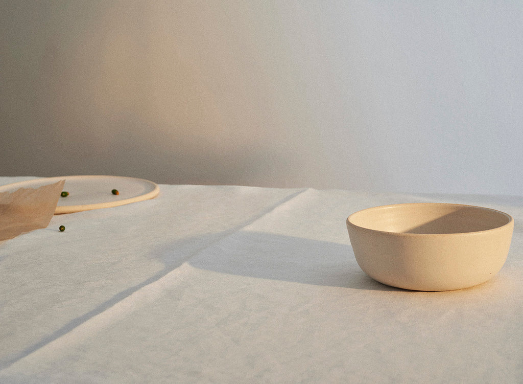 A handmade Sheldon Ceramics Silverlake Low Profile Bowl in Eggshell casts a long shadow across a white linen tablecloth.