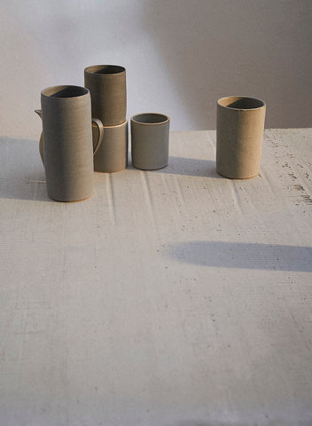 A grouping of handmade Sheldon Ceramics Cylinder Vases and Silverlake Tumblers in a variety of grey glazes.
