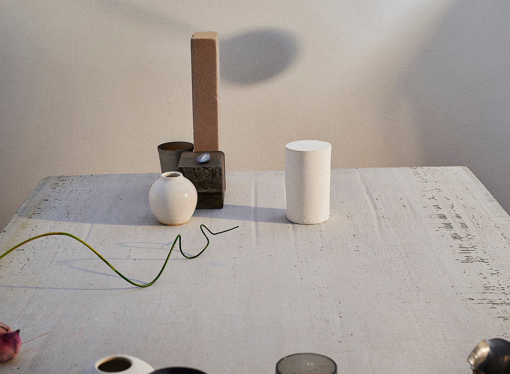 A white table scattered with an assortment of objects: a handmade ceramic vase, a brick, a length of green wire, and an aluminum tin.