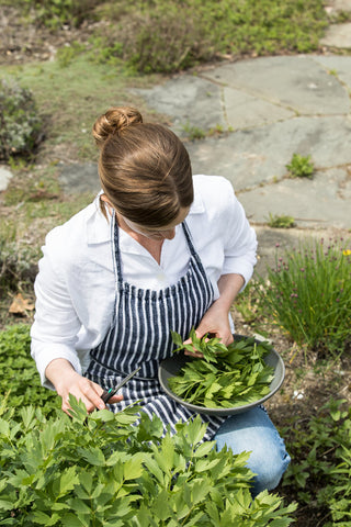 Annemarie Ahearn harvests parsley at Salt Water Farm, filling a handmade ceramic bowl with freshly snipped stems.