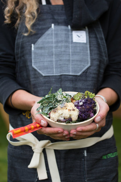 Heidi Rentz of The Cyclist's Menu holds a handmade ceramic bowl filled with colorful roasted vegetables.