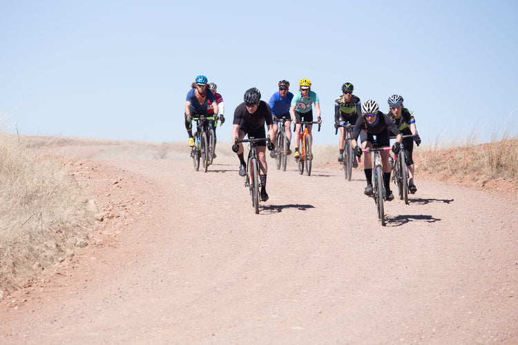 A group of Cyclist's Menu members ride bikes down a winding dirt path.