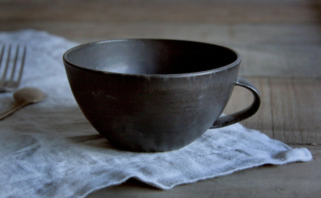 Handmade Pottery Latte Cup in Black on Napkin