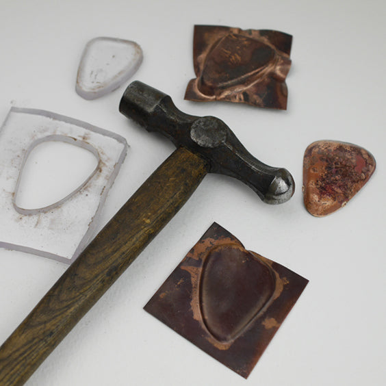 Acrylic press forming tool, copper samples and vintage hammer all part of the process of making the necklace