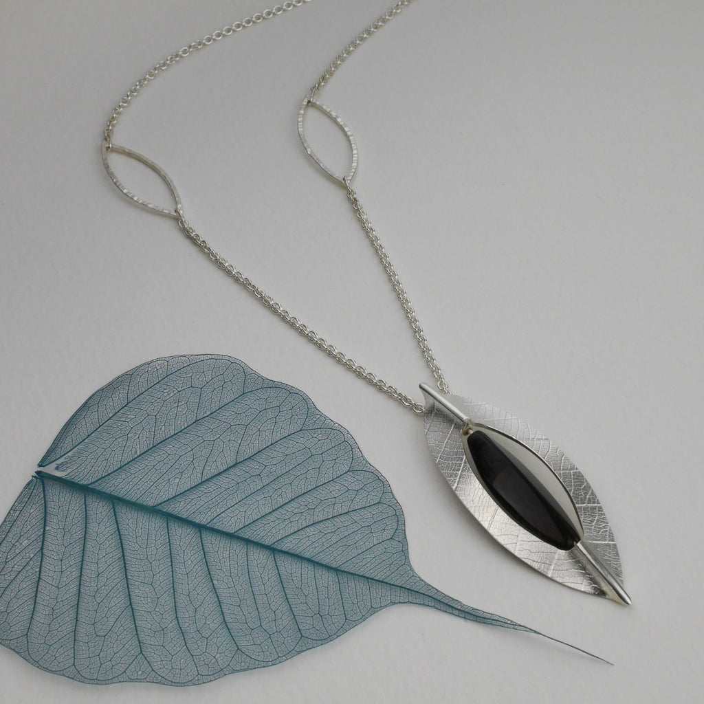 p>The pendant hangs from a continuous 'over the head' chain, with the additionof two hammered leaf outline details