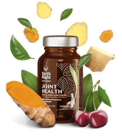 Joint Health supplement in sustainable glass bottle surrounded by turmeric, boswellia, tart cherry, ginger root, and other wellness herbs and spices